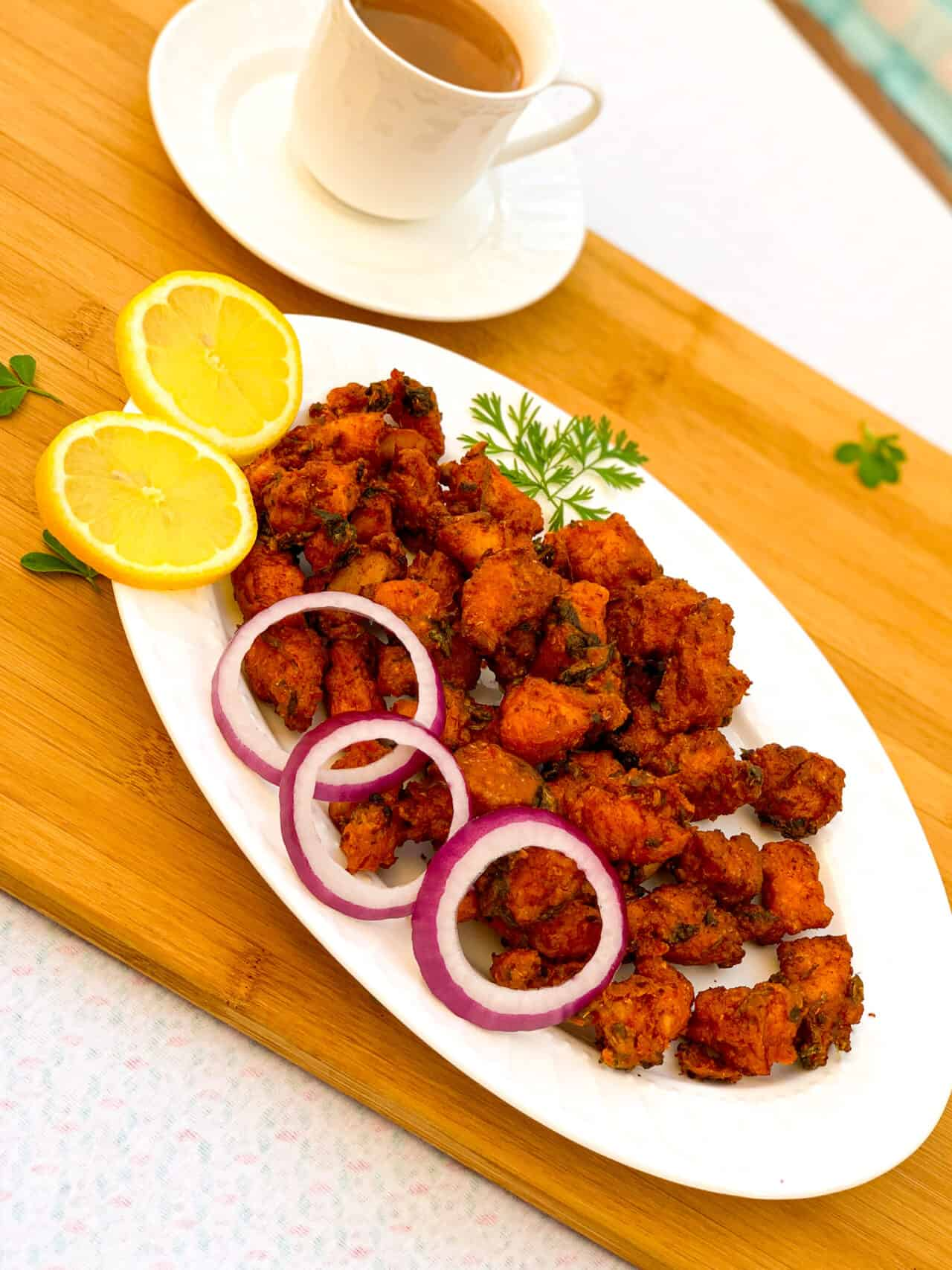 Plate of chicken fritters with lemon and onion rings with chai or tea in the background