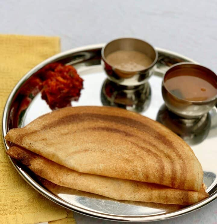 Crispy dosas on a plate with chutney, sambhar and pickle