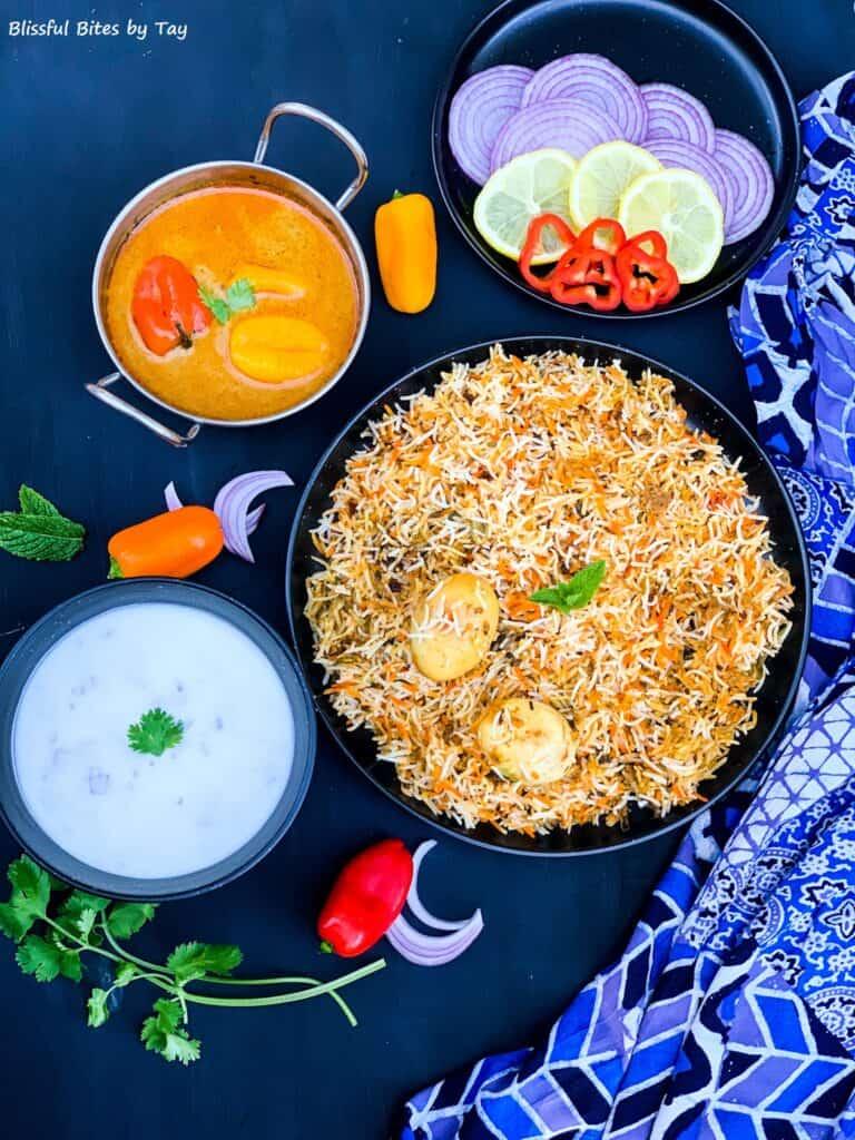Egg biryani served with mirchi ka salan, raita, onion and lemon slices.