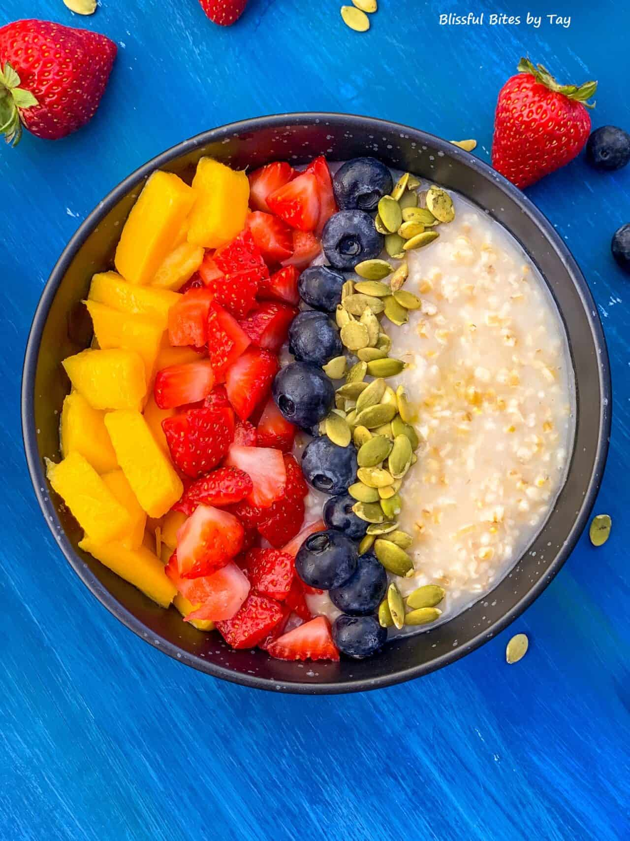 Steel cut oatmeal in a black bowl with mango, strawberry, blueberry and pumpkin seeds.