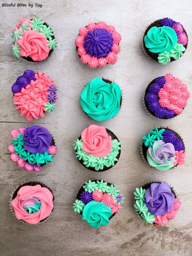 Chocolate cupcakes with teal, pink and purple flowered frosting.