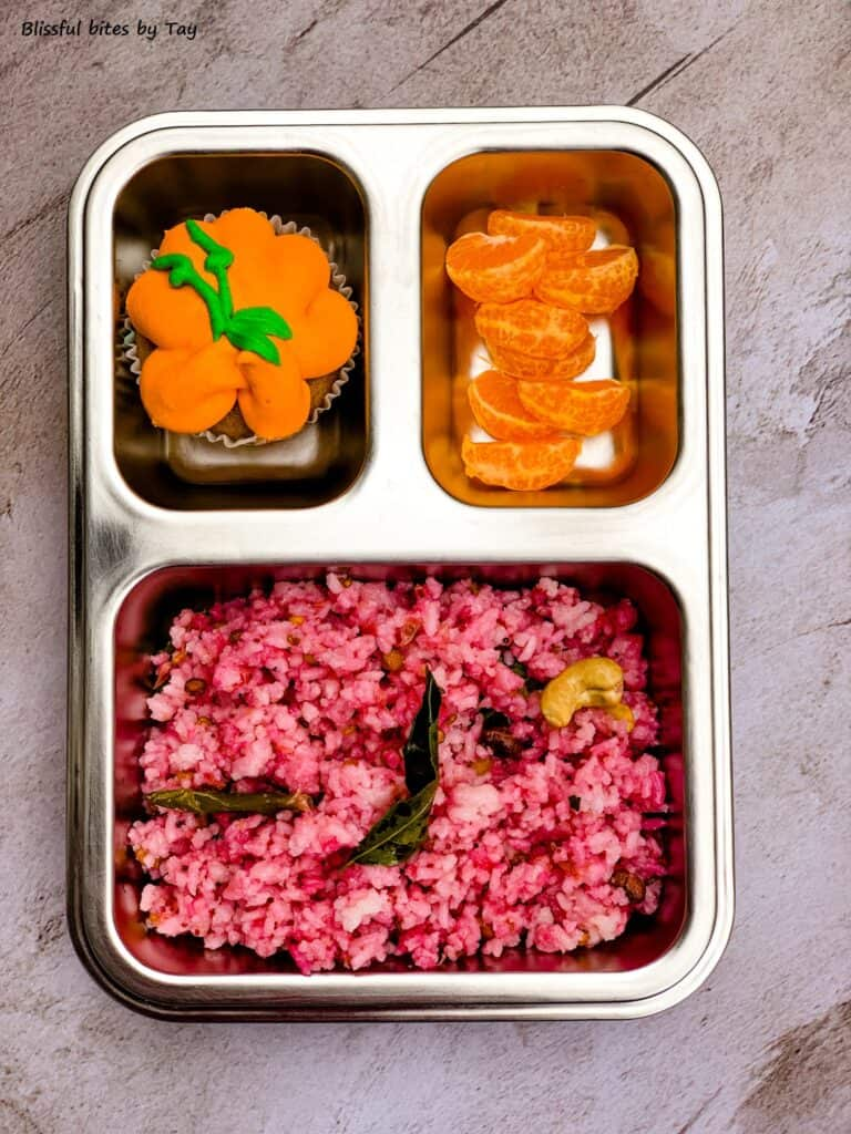 Lunchbox with cranberry rice, pumpkin cupcakes and clementine.