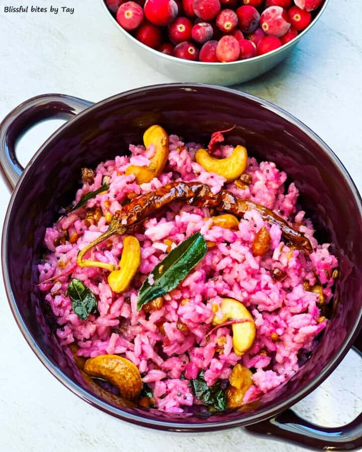 Cranberry rice with cashews on top and cranberries in the background.