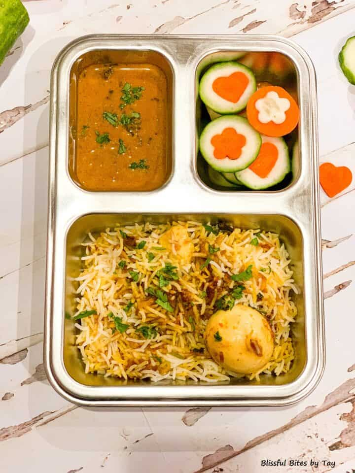 Egg Biryani with mirchi ka salan and carrot and cucumber veggies shapes.